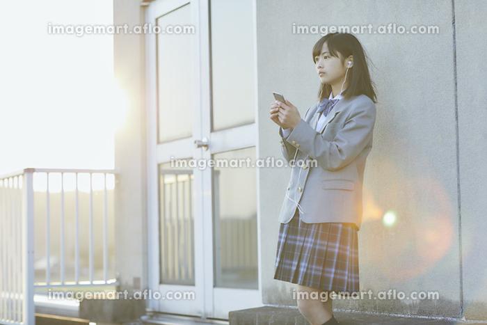 学校の屋上で音楽を聴く女子中学生