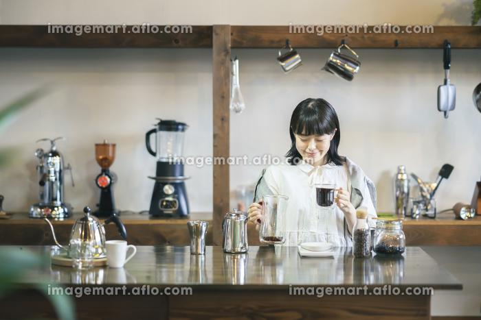 おしゃれな空間で、コーヒーを淹れる若い女性の販売画像