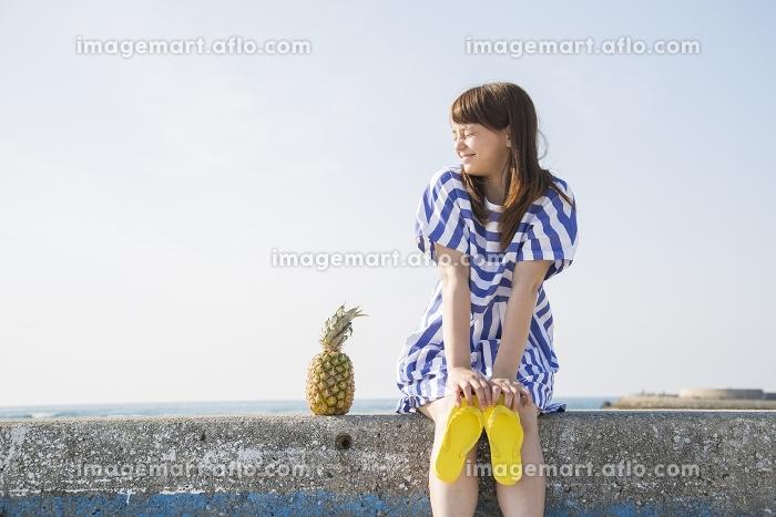 堤防に座る日本人女性とパイナップル