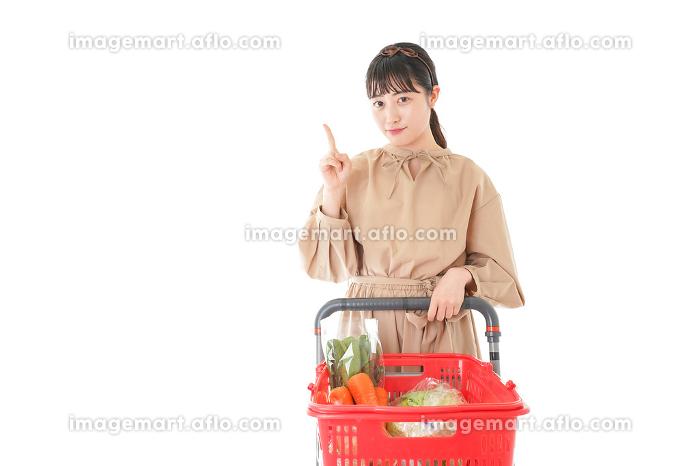 スーパーで指をさす若い女性の販売画像