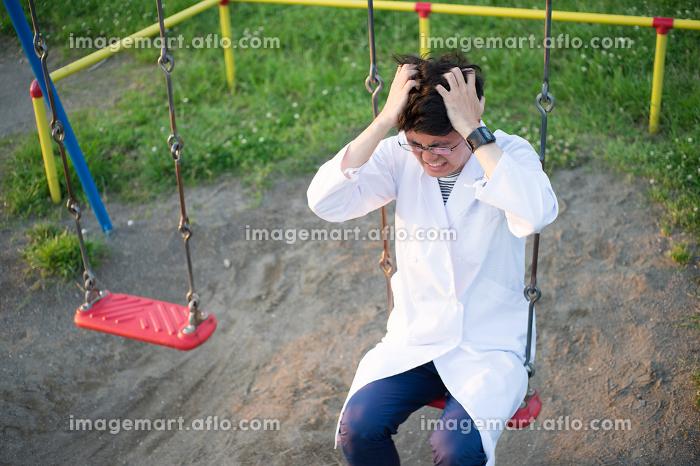 公園で苦悩する白衣の男性(医者・科学者・学者・医療従事者イメージ)の販売画像