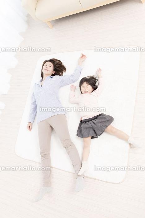 フローリングに寝転がる母と娘