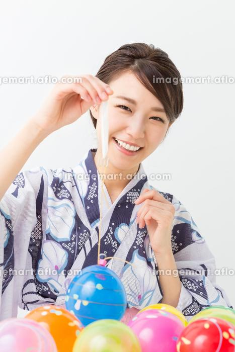 浴衣を着てヨーヨーを持つ女性の販売画像