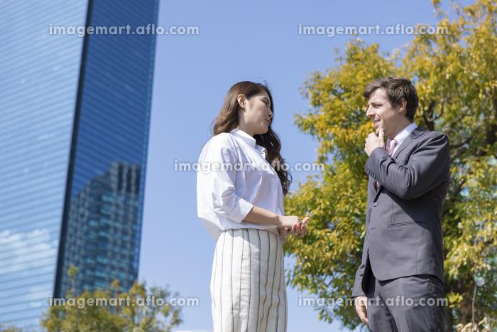 会話をするビジネスマンとビジネスウーマンの販売画像