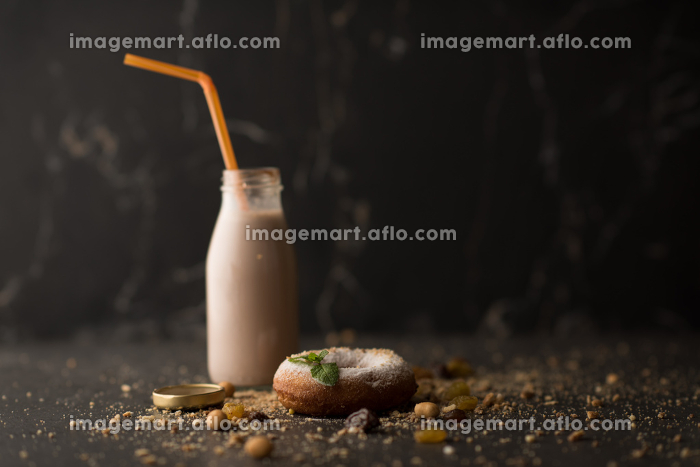 Sugar powder Donut with mint leaf and milk bottle on dark stone background