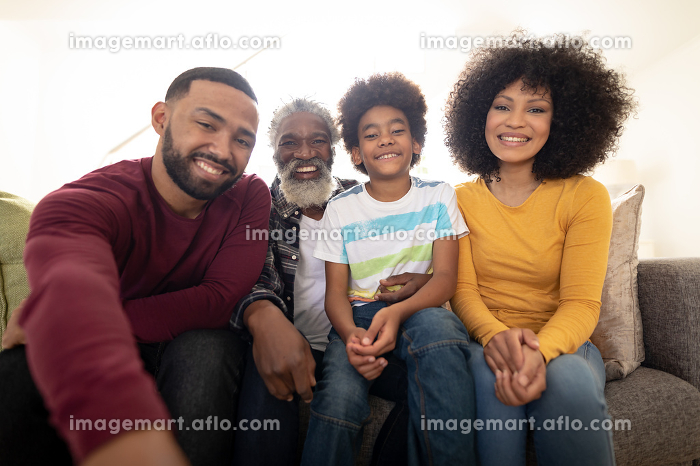 Portrait of multi generation African American family at home sitting on sofa in living room, smiling to camera. Family spending quality time at home together in slow motion.の販売画像