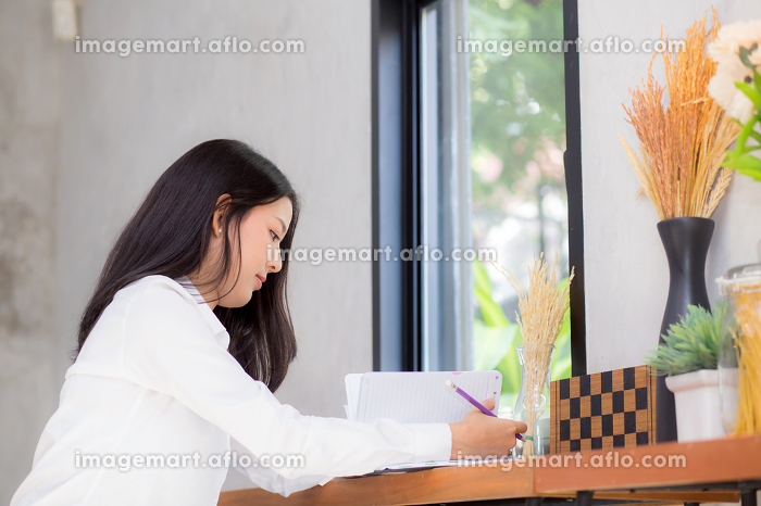 Beautiful business asian young woman writing on notebook on tabl