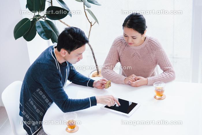 ネットショッピングの決済をクレジットカードで行うカップルの販売画像