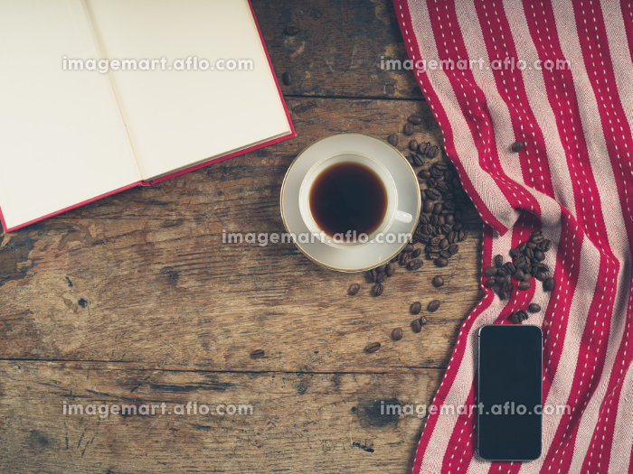 Overhead shot of coffee concept with cup, tea towel, an open book and a smart phone