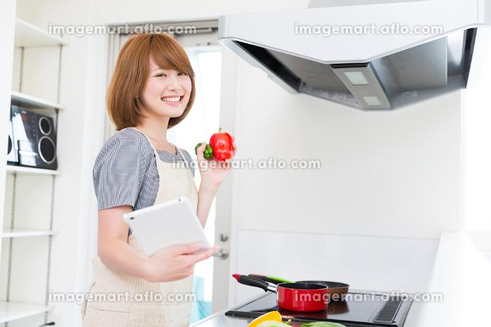 タブレットを見ながら料理をする女性の販売画像