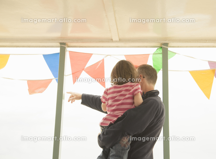Man with child looking out past bunting