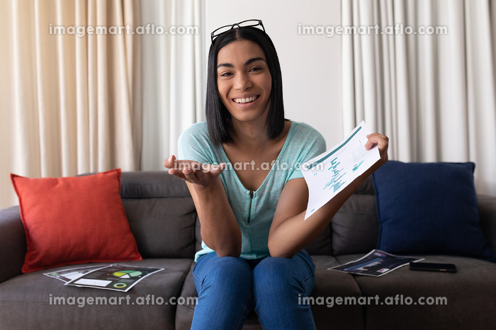 Mixed race gender fluid man working at home making video call holding documents and smiling. staying at home in isolation during quarantine lockdown.の販売画像