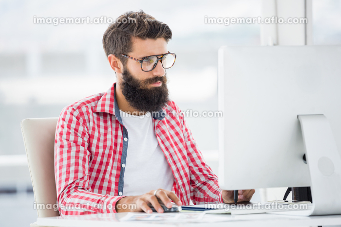 Hipster man is typing on his computerの販売画像