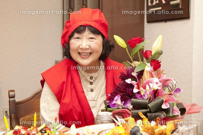 赤い服で祝う還暦女性の販売画像