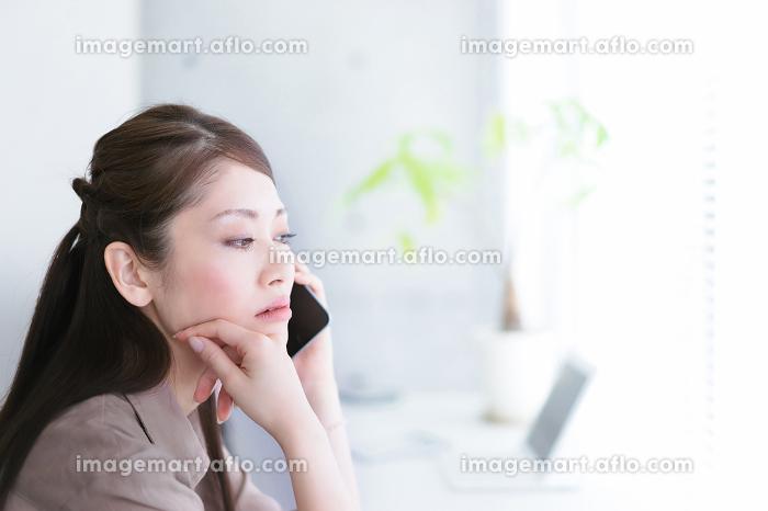 窓際で通話をする若い女性の販売画像