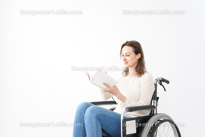 車椅子に乗り読書をする外国人の女性の販売画像