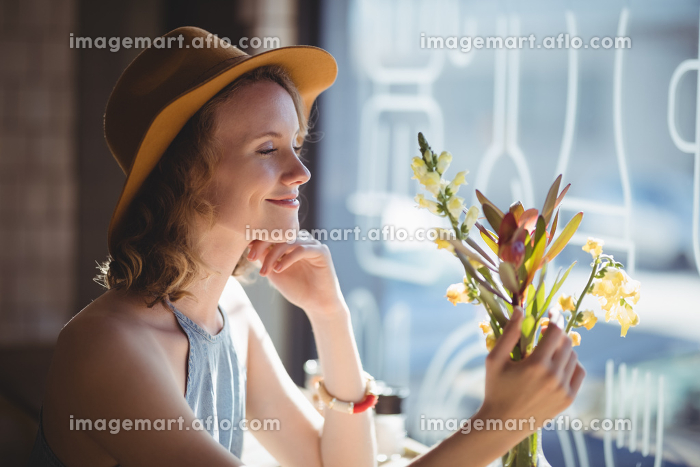 Smiling young woman looking at flower against windowの販売画像