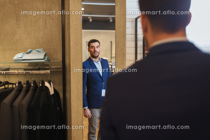 man trying jacket on at mirror in clothing storeの販売画像