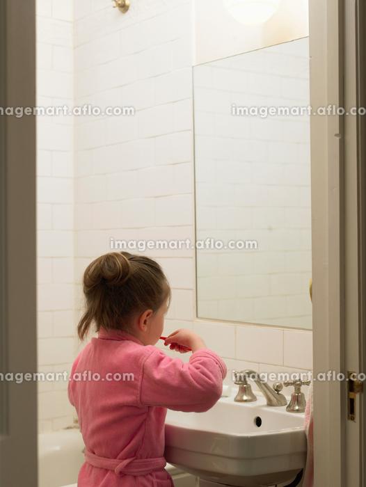 Girl brushing her teeth in bathroomの販売画像