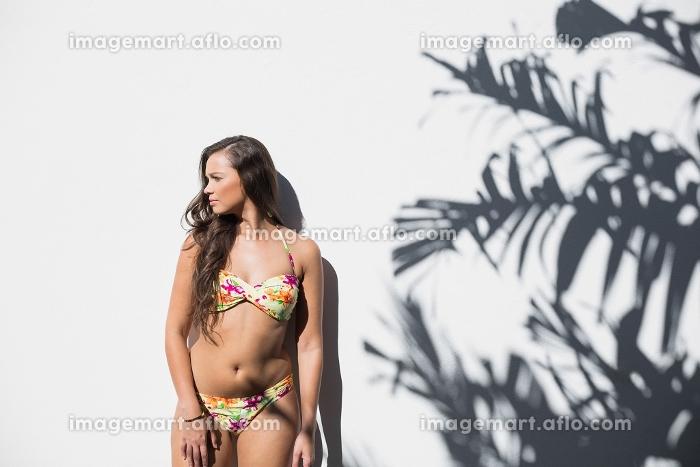 Sexy woman in flowery bikini posing on white wall with palm tree shadowの販売画像