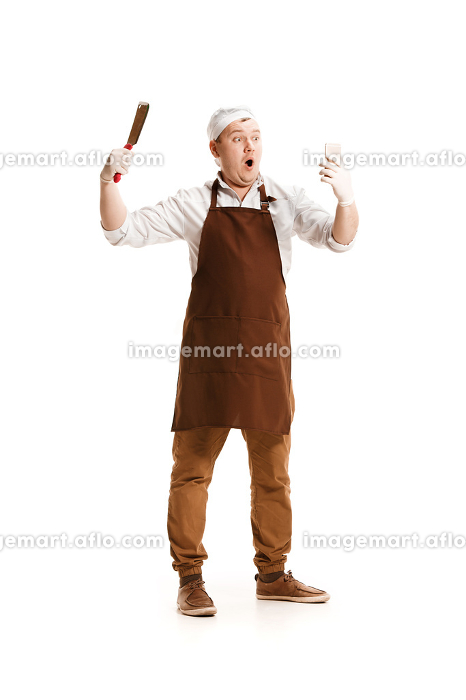 Smiling butcher posing with a cleaver isolated on white backgroundの販売画像