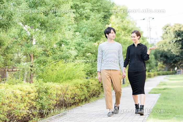 手を繋いで散歩をする国際カップル(欧米人とアジア人)の販売画像