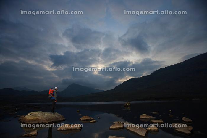 Hiker standing on rocks in a lake.