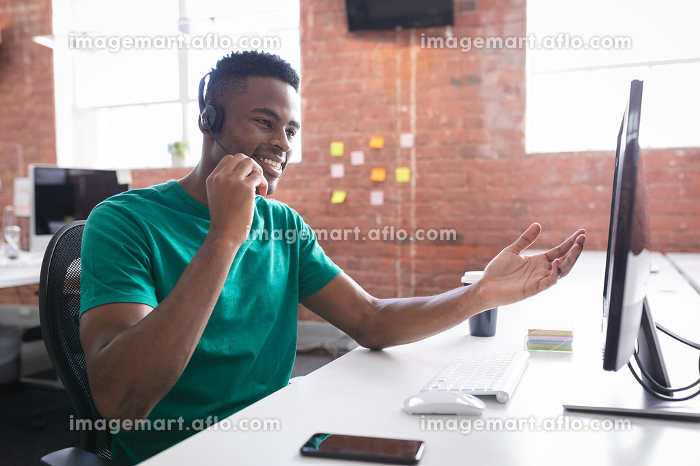 African american businessman having video call sitting in front of computer using headphones. independent creative design business.の販売画像