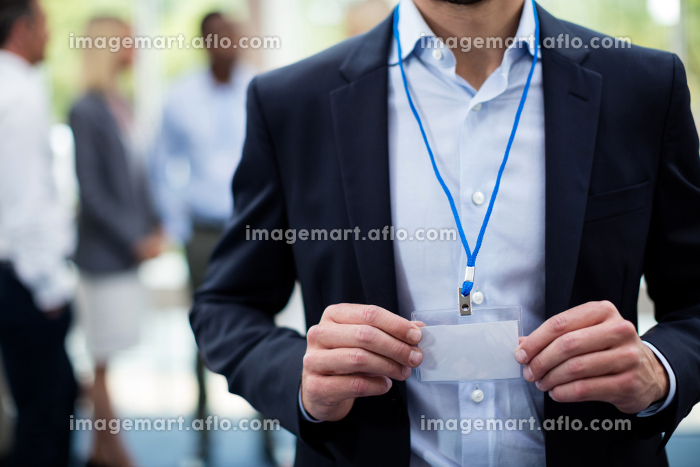 Mid section of employee showing Id cardの販売画像
