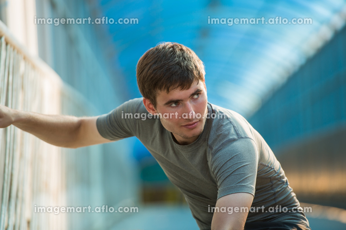 Man stretching outdoors in city before joggingの販売画像