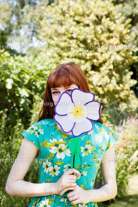 woman peeping from behind fabric flower.の販売画像