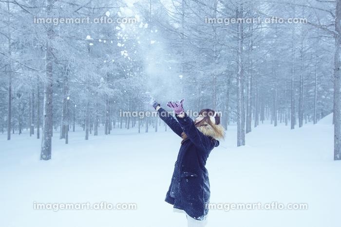 森の中で雪を舞い上げる女性の販売画像