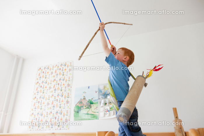 Boy playing with toy bow and arrowの販売画像