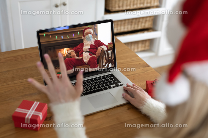 Caucasian woman spending time at home at Christmas, using laptop computer, video chatting with Santa Claus in face mask and waving. Social distancing during Covid 19 Coronavirus quarantine lockdown.の販売画像
