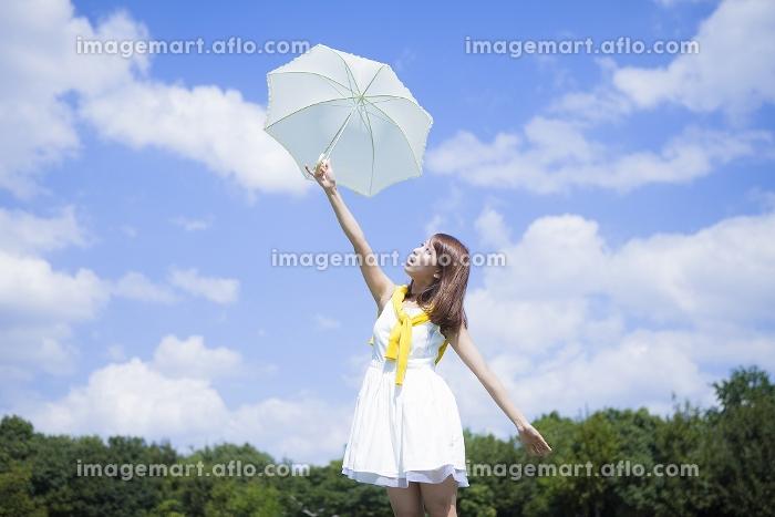 青空の下飛ばされそうな日傘をつかむ女性