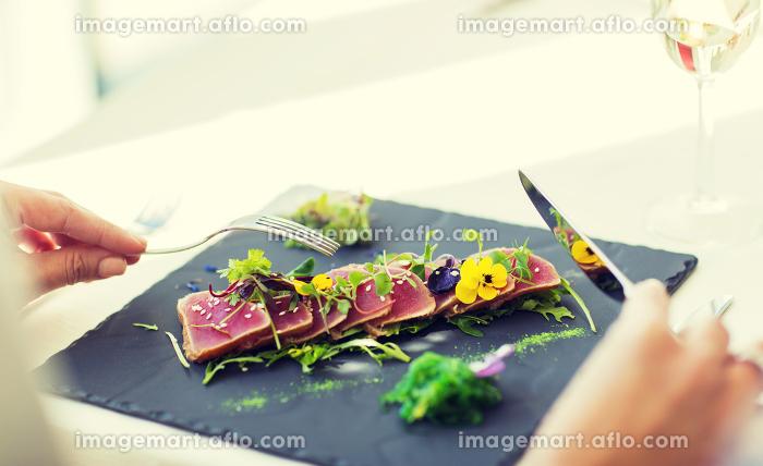 close up of woman eating salad at restaurantの販売画像