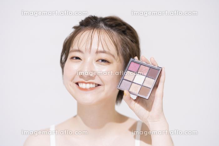 コスメアイテムを持つ若い女性の販売画像