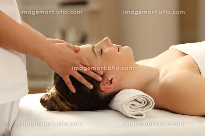Woman relaxing receiving a facial massageの販売画像