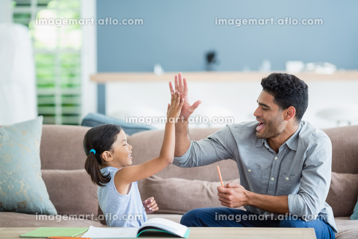 Father giving high five to daughter while helping her in homeworkの販売画像