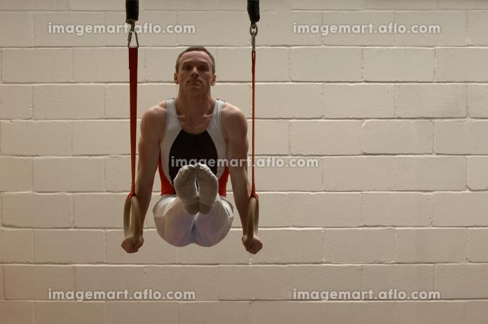 Male gymnast balancing on ringsの販売画像