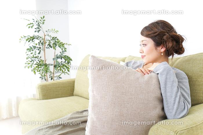 家でリラックスする一人暮らしの女性の販売画像