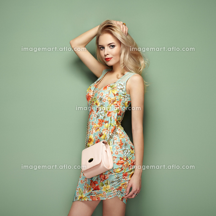 Blonde young woman in floral summer dress. Girl posing on a green background. Jewelry and hairstyle. Girl with handbag. Fashion photo