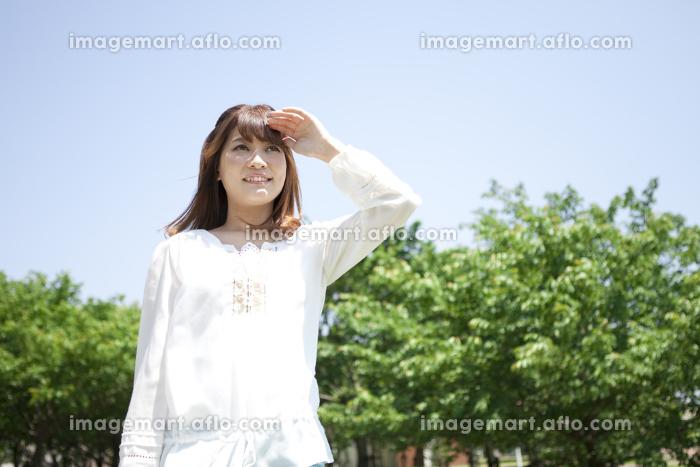 遠くを眺める笑顔の女性