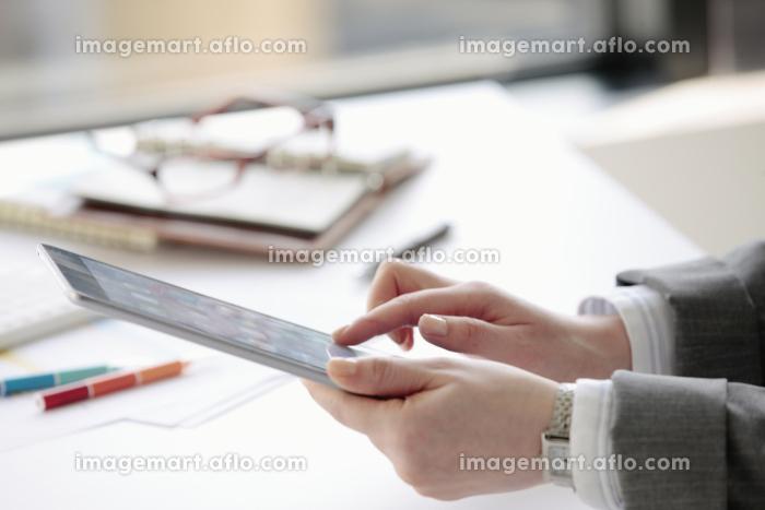 タブレットPCを操作するビジネスウーマンの手元の販売画像