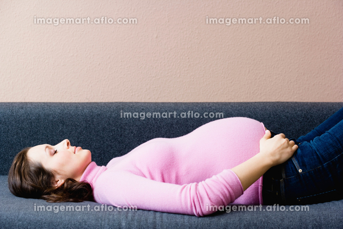 Pregnant woman laying on couchの販売画像