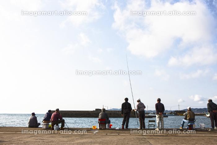 堤防で釣りをする人の販売画像