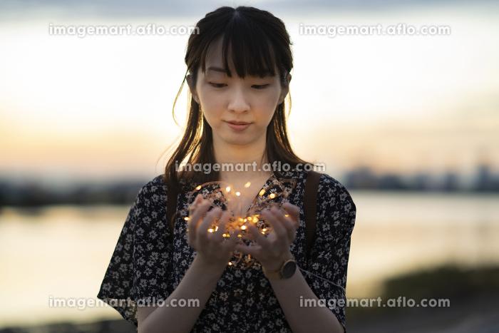 イルミネーションライトを両手で包む若い女性の販売画像
