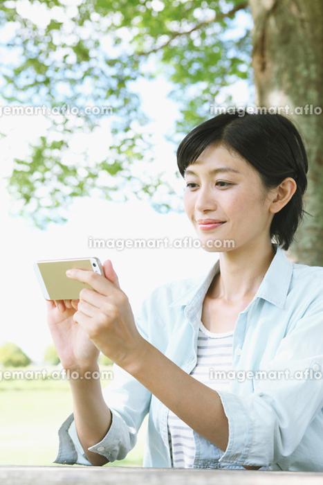 新緑と携帯を見る日本人女性