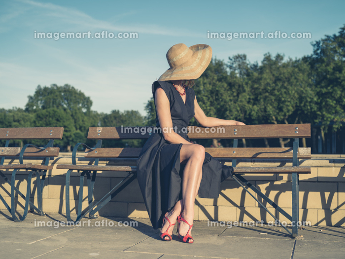Vintage filtered shot of an elegant young woman in dress and high heels sitting on a park bench
