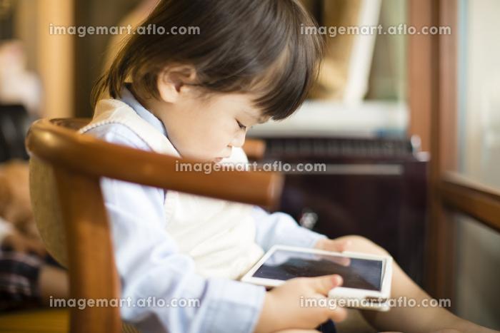タブレット型コンピューターを見る男の子の販売画像